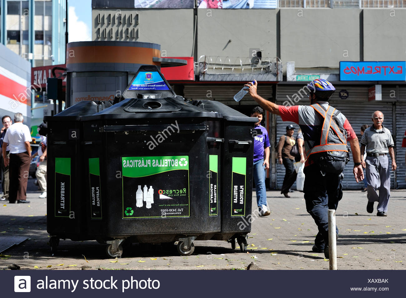 Man throwing a plastic bottle into a container for recyclables, waste separation and recycling, pedestrian zone of San José - Stock Image