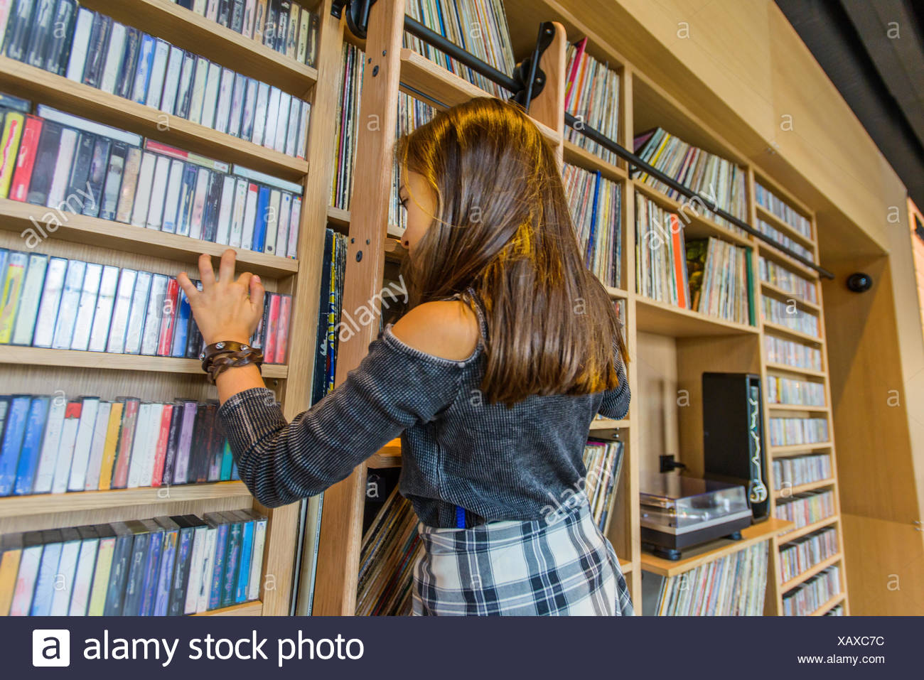Girl searching cassette tapes on shelf - Stock Image