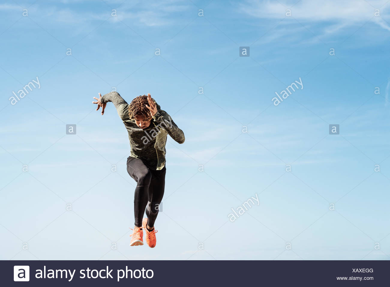Young man running outdoors, mid air Stock Photo