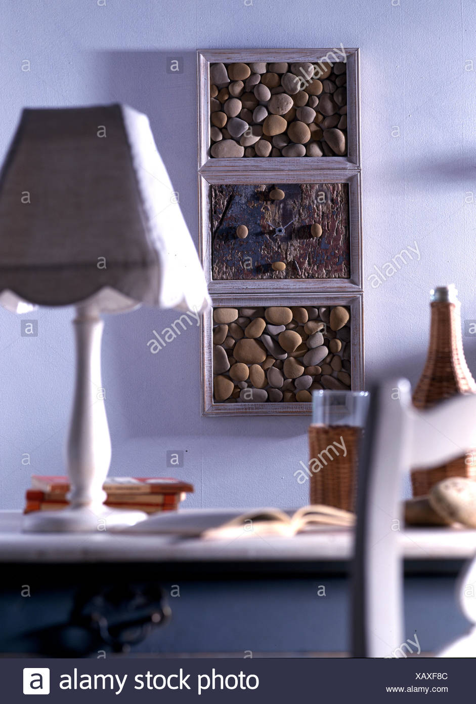 Seashore pebbles in box frame on wall - Stock Image