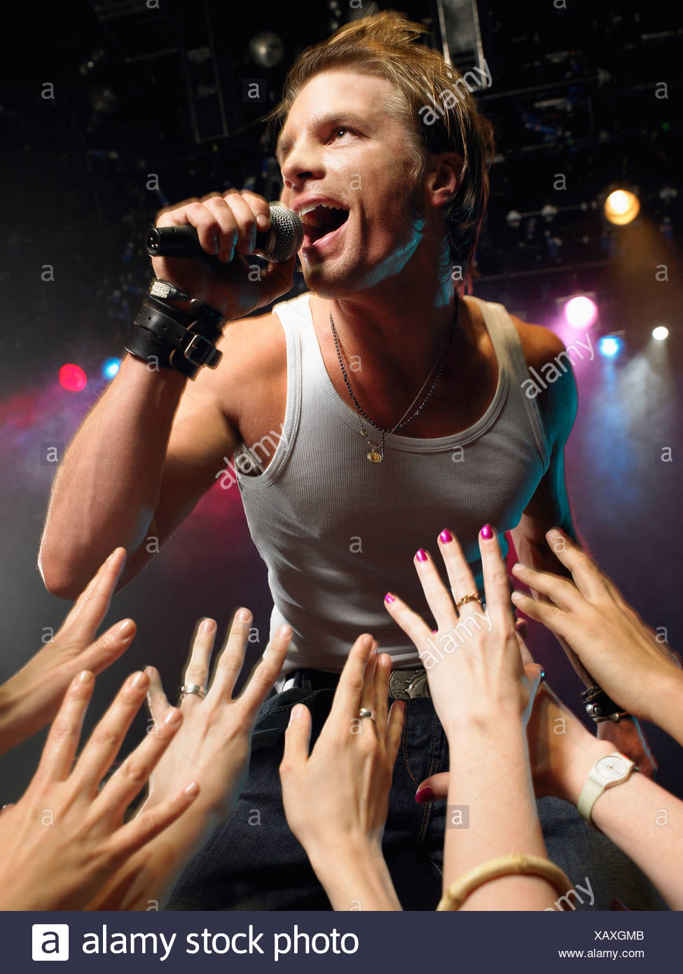 Low angle view of male rock star singing on stage with adoring fans reaching their hands up towards him - Stock Image