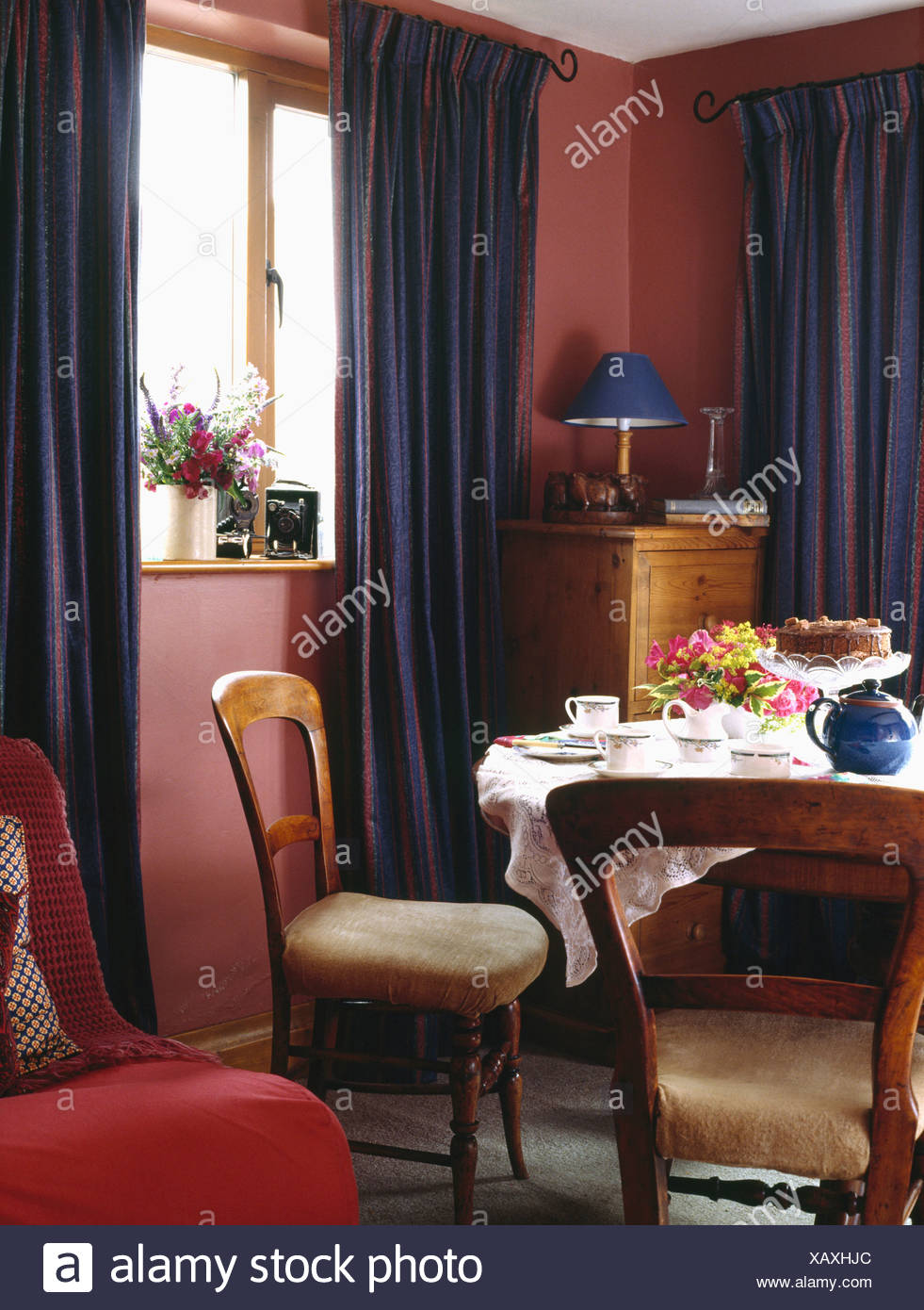 Dark Blue Curtains And Antique Chairs In Small Red Country Dining Room With Teaset On The Table Stock Photo Alamy