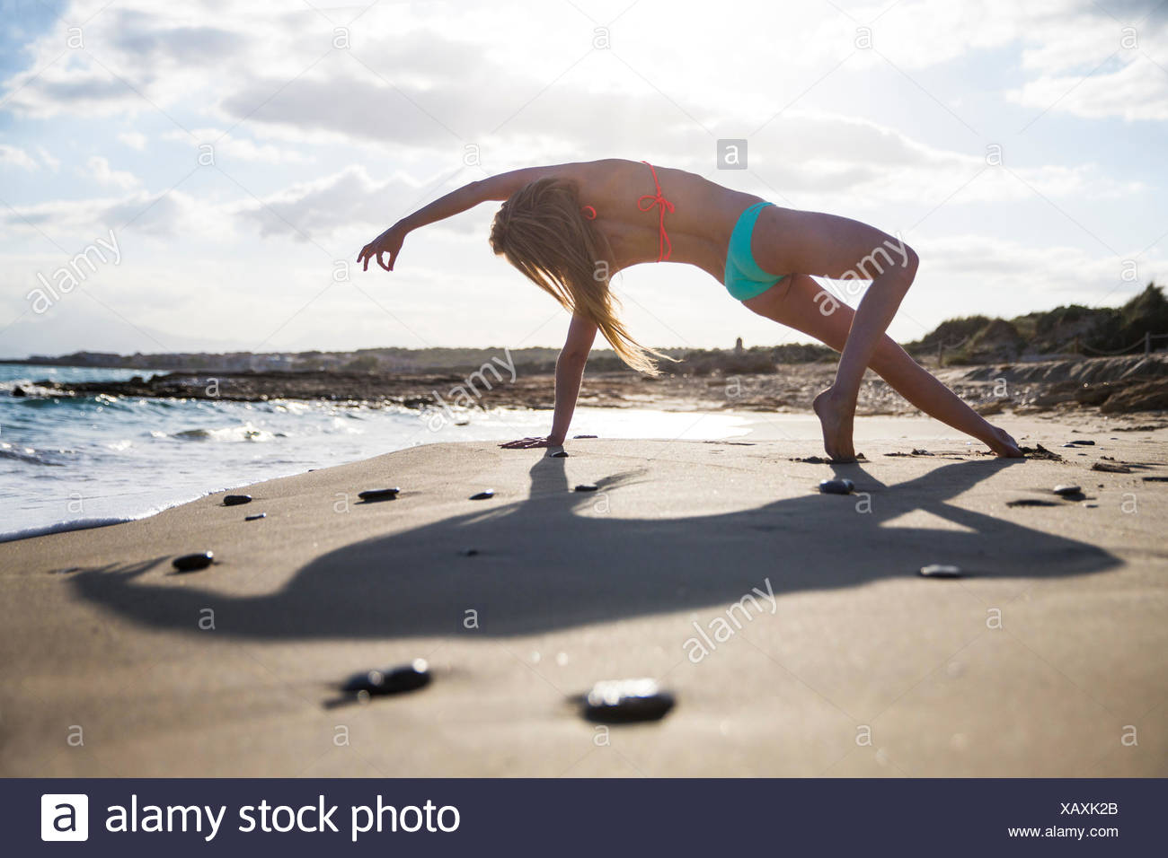 Young woman on beach, in yoga position, rear view - Stock Image