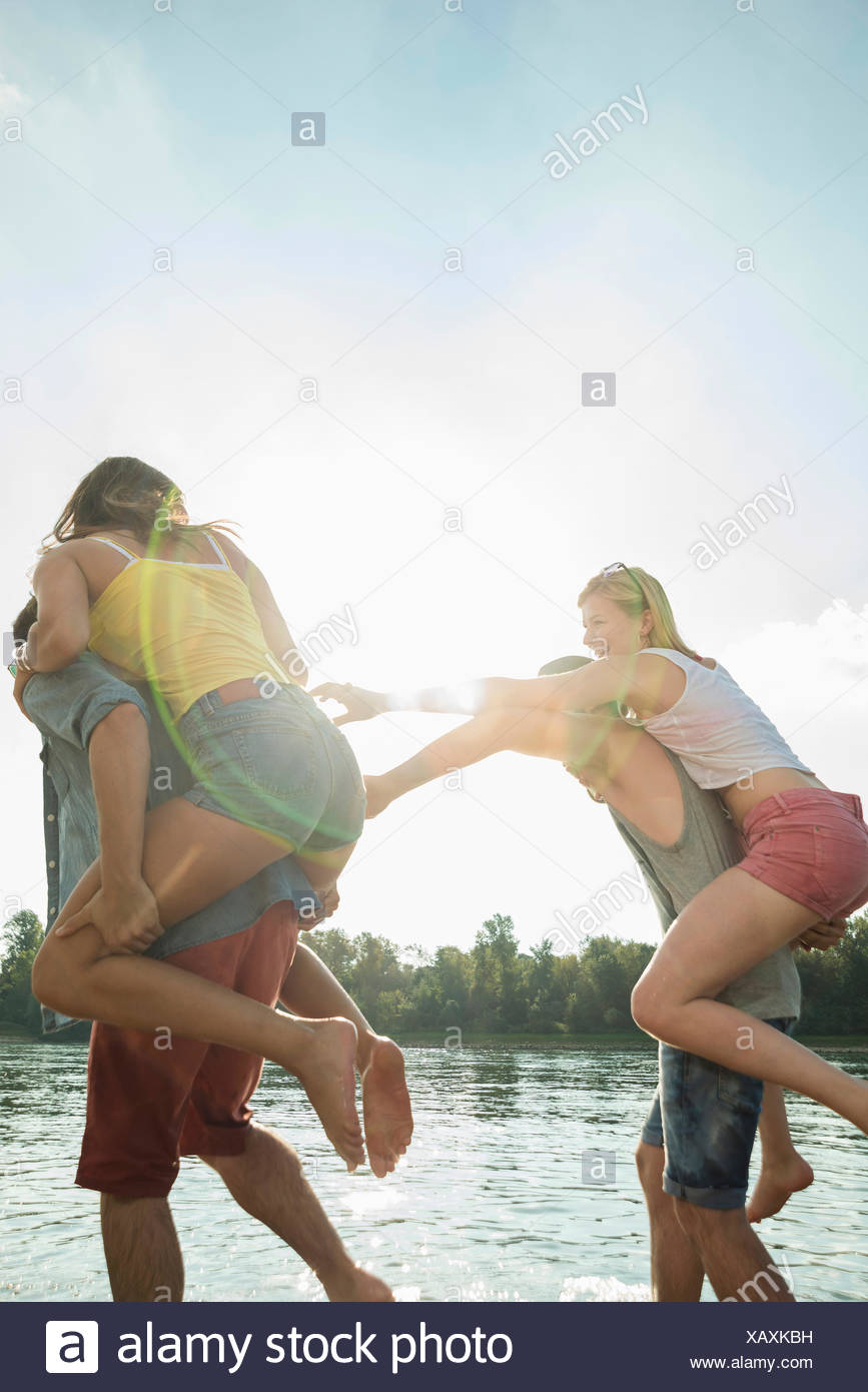 Young men giving young women piggy backs - Stock Image