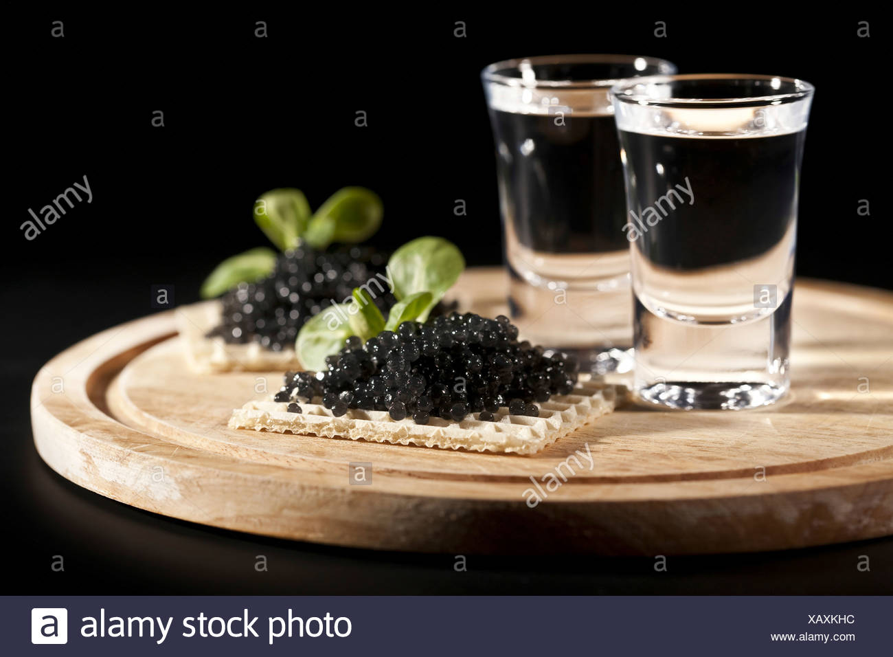served place setting: vodka and sandwiches with black caviar on black background - Stock Image