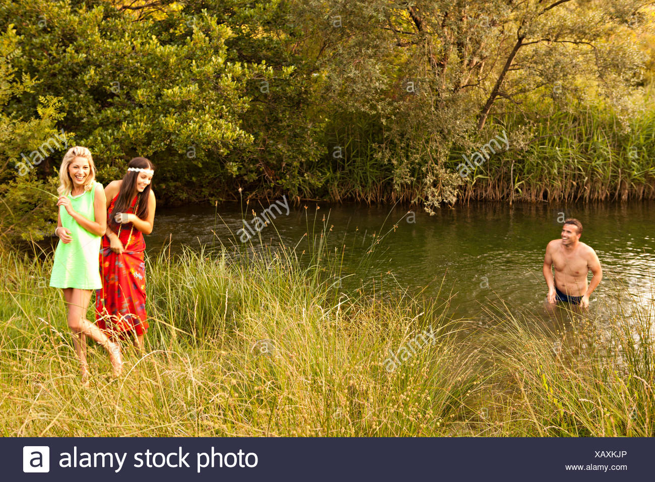 Croatia, Dalmatia, Man stands in lake, women on water's edge - Stock Image