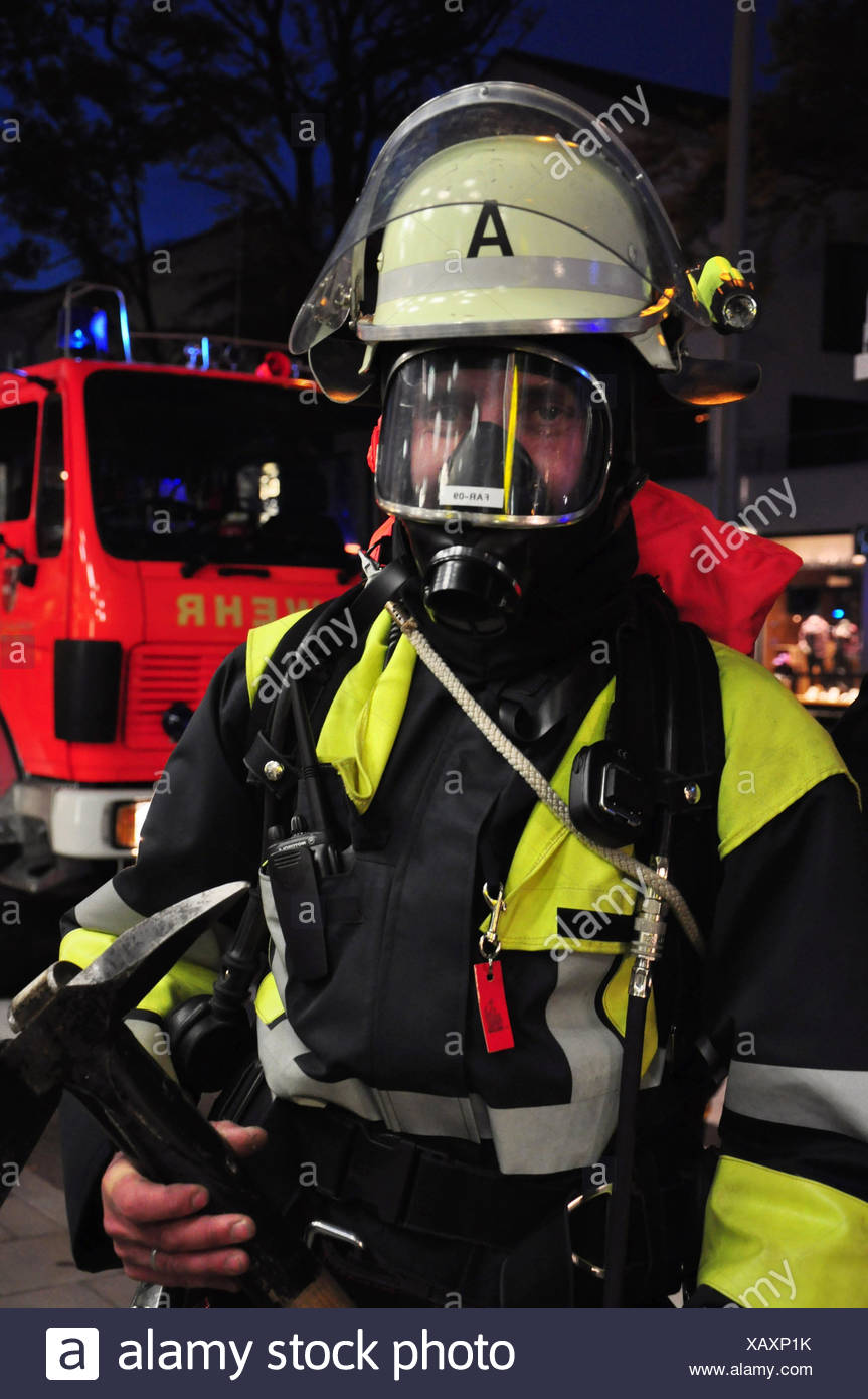 Firefighter,respiration protection,respirator,protective mask,mask,helmet,human rescue,life rescue,firefighting,occupation,man,person,evening,in an honourary capacity,portrait,curled, - Stock Image