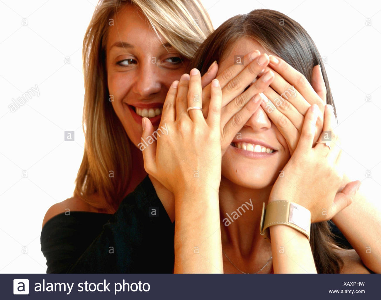a blond and a brunette young women playing peekaboo - Stock Image