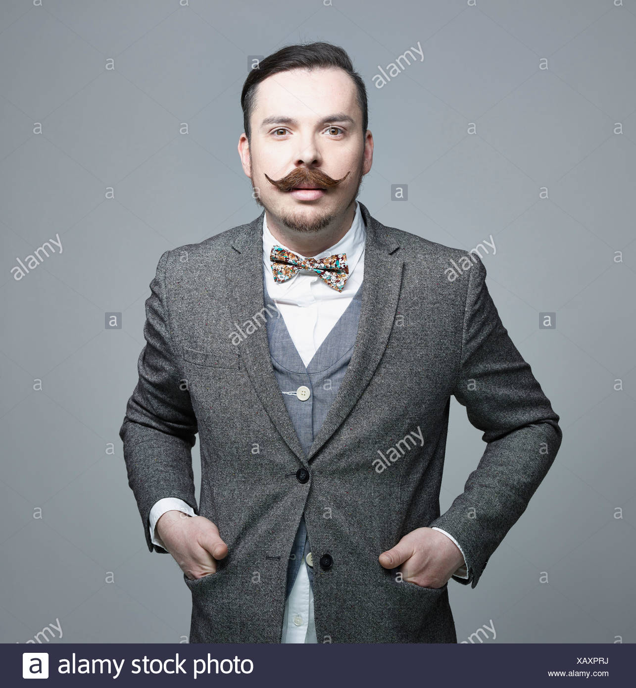 Portrait of mid adult man against grey background, smiling - Stock Image
