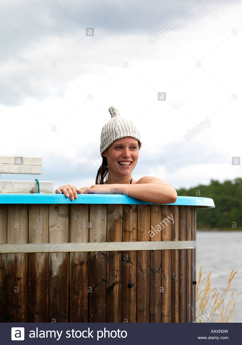 Woman bathing in tub by sea - Stock Image
