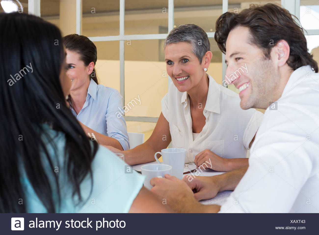 Business people smile and chat while enjoying hot drinks - Stock Image