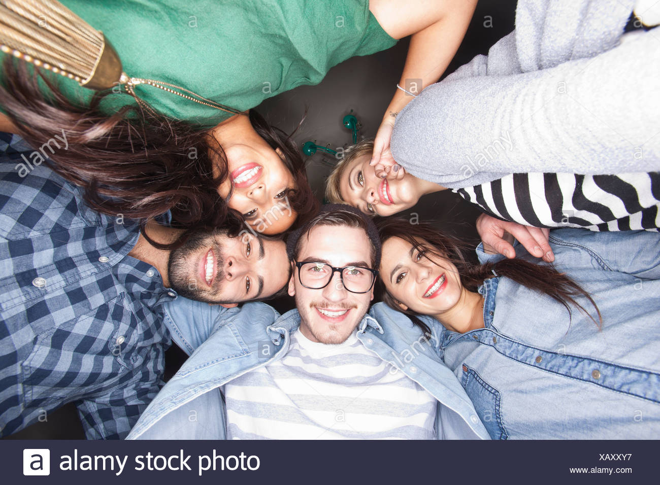 Friends smiling together in circle - Stock Image