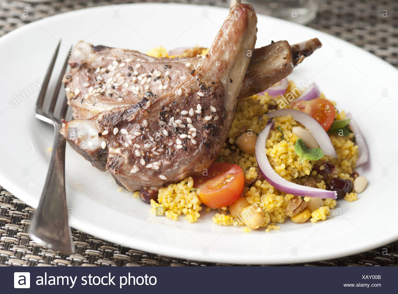 Sesame Lamb cutlets with nutty couscous on a plate. - Stock Image
