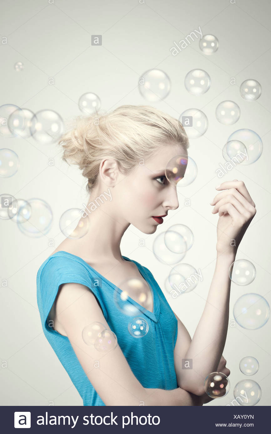 Young woman surrounded by bubbles, portrait - Stock Image