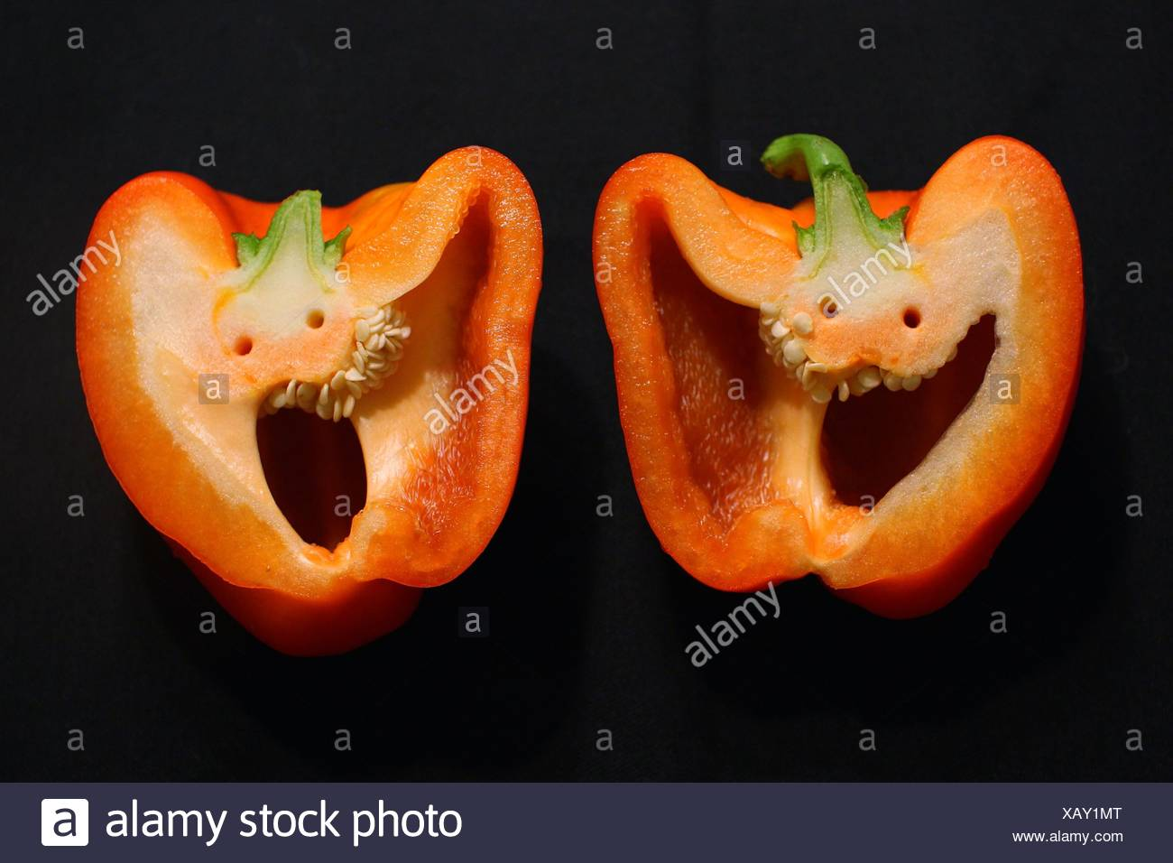 Cut Orange Bell Pepper Against Black Background - Stock Image