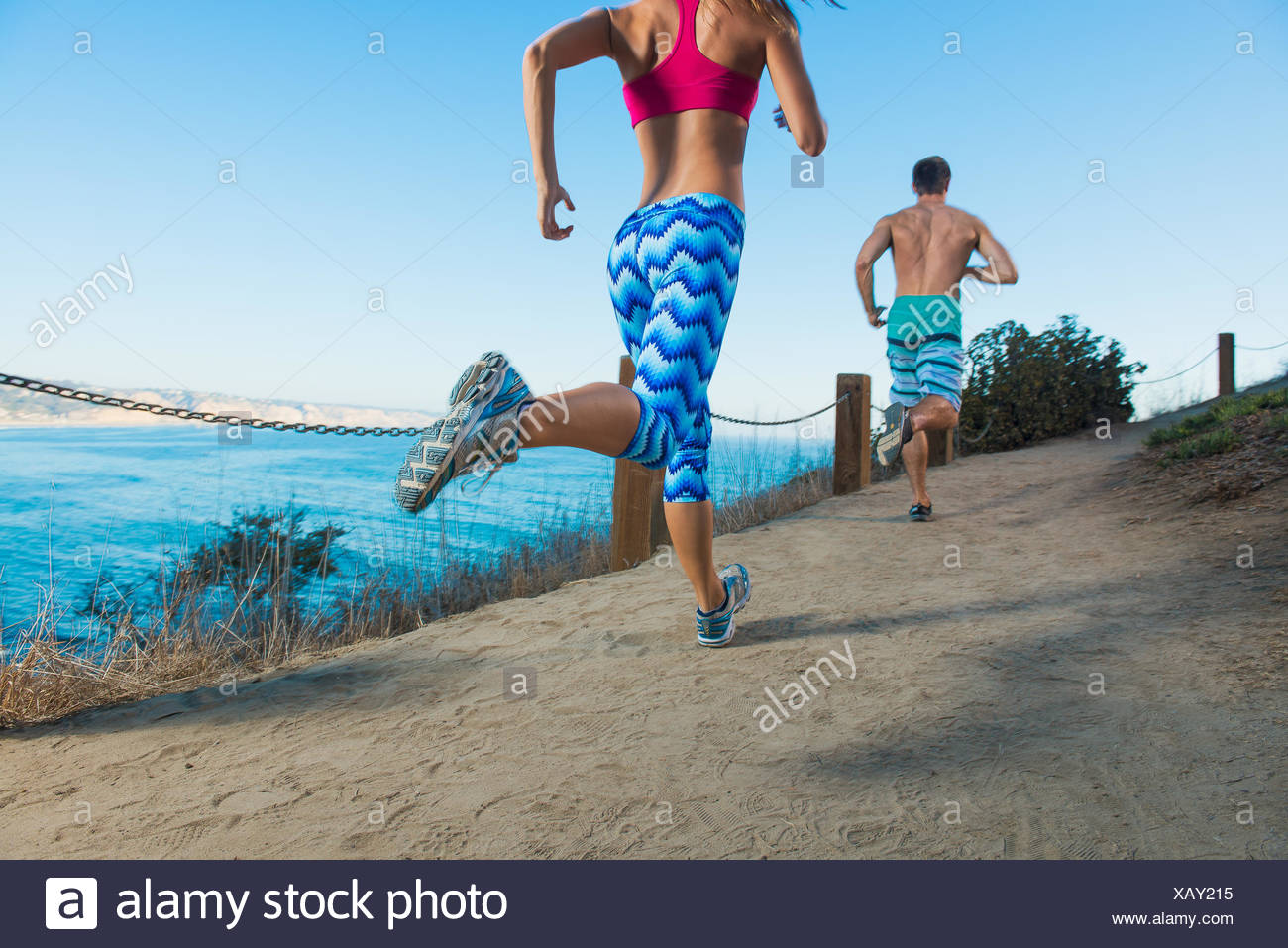 Mid adult man and young woman running on path by sea, rear view - Stock Image