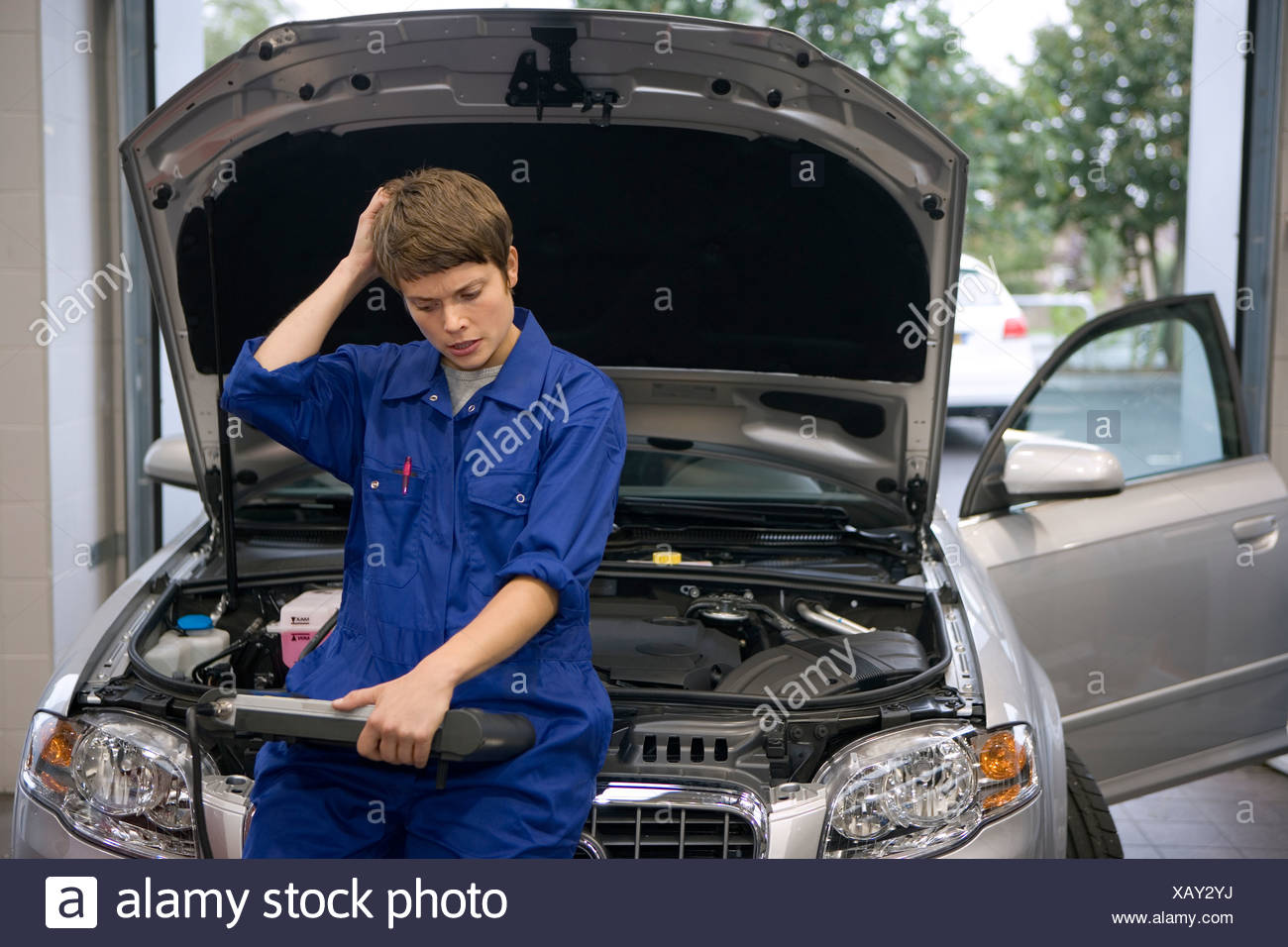 Female mechanic looking at diagnostic computer by open bonnet of car, hand to head Stock Photo