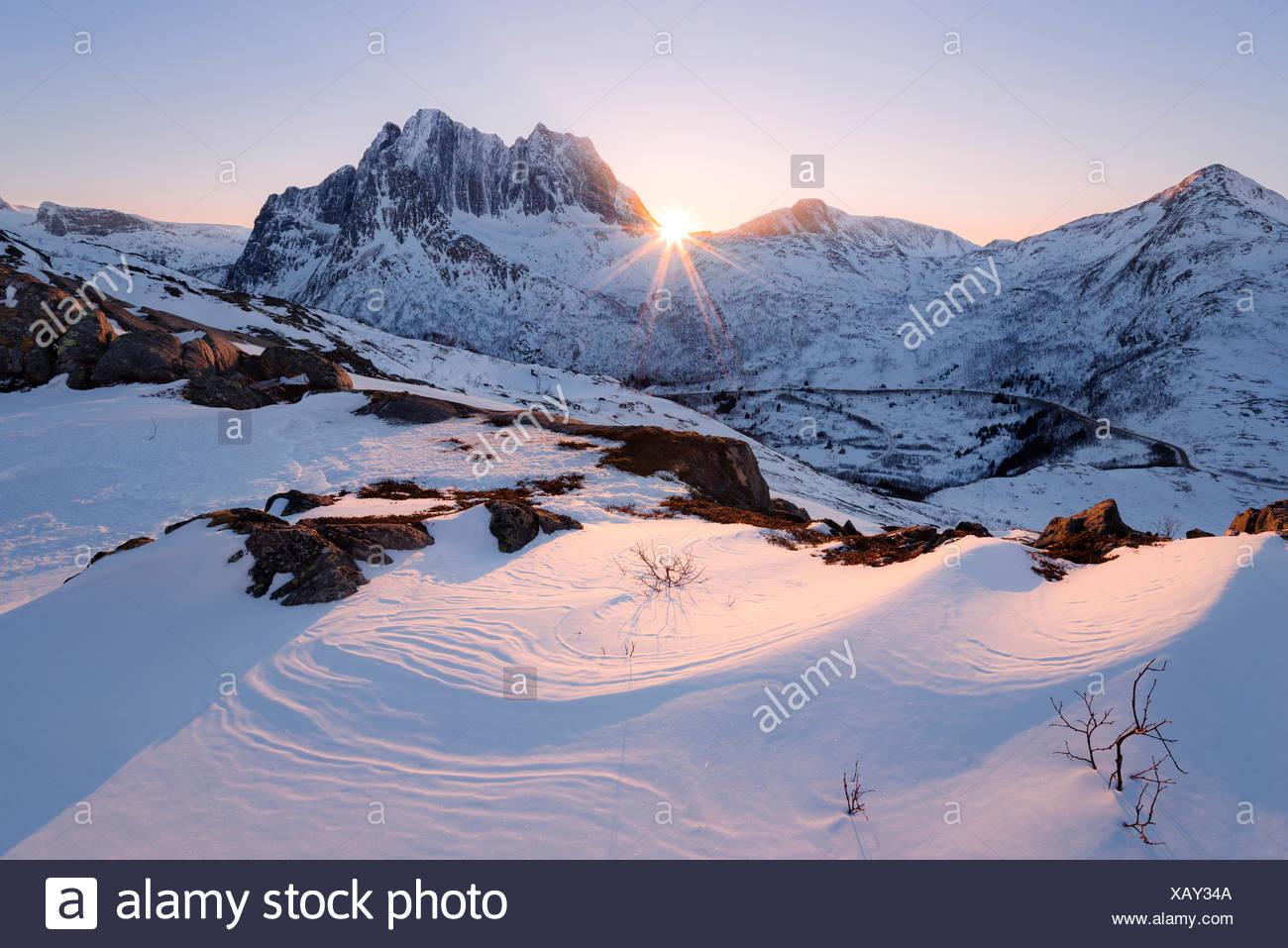 Norway, Nordland, Senja, island, mountain, back light, sun, star, rays, light, curved, snow, winter, soft, bizarre, summit, scenery - Stock Image