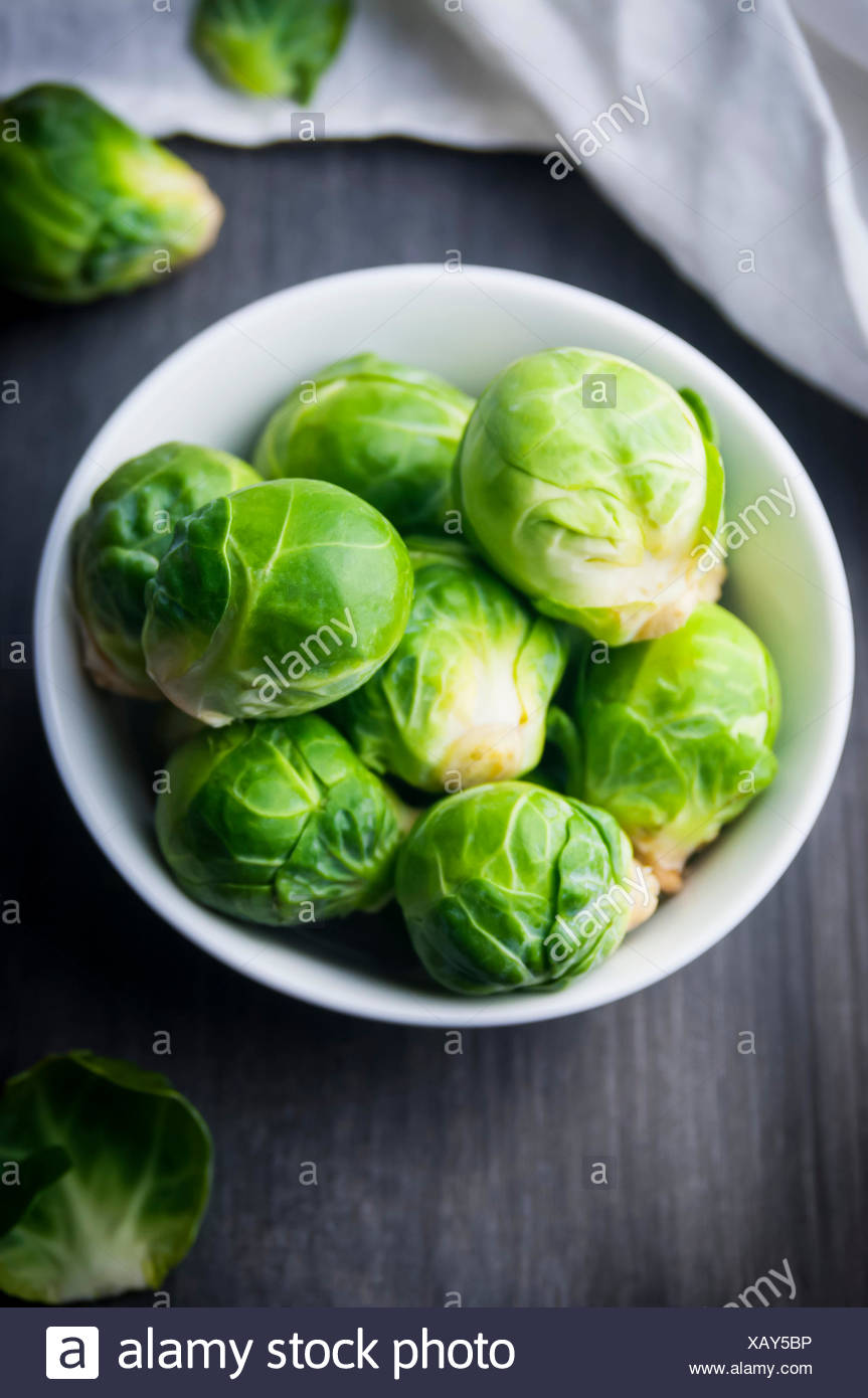 A Close Up of a Bowl of Fresh Brussels Sprouts - Stock Image