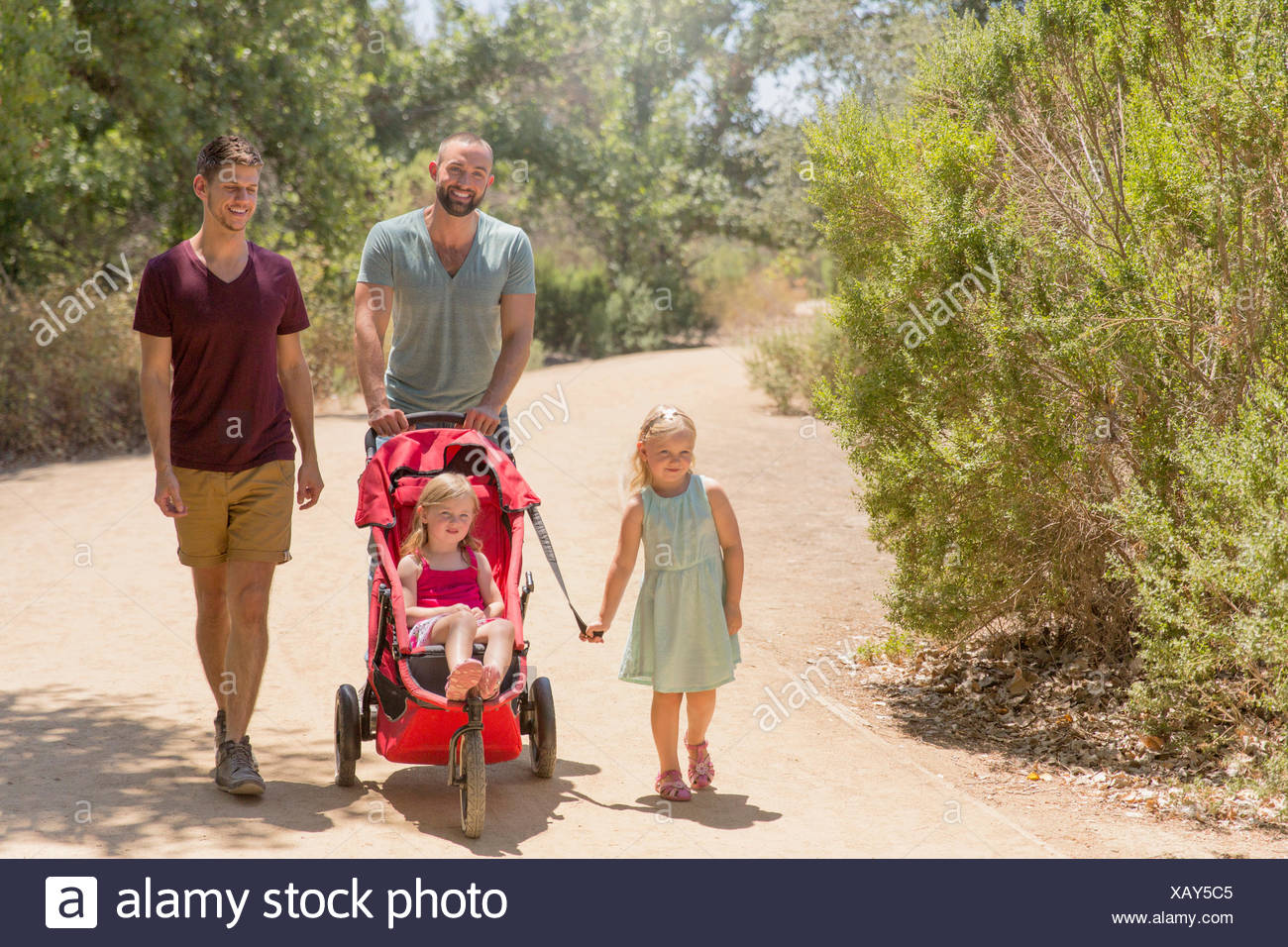 Male couple strolling with two daughters in park - Stock Image