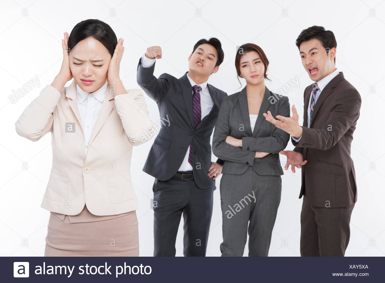 One stressful business woman excluded by other coworkers - Stock Image