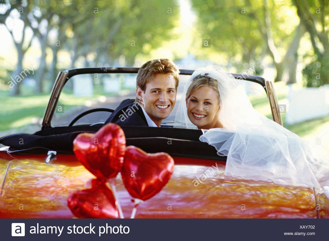 Bride and groom in red convertible, heart shaped balloons tied to bumper - Stock Image