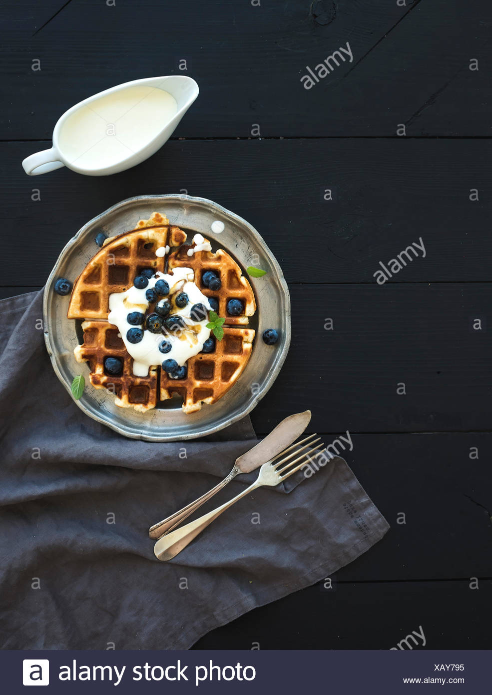 Soft Belgian waffles with blueberries, honey and whipped cream on vintage metal plate over black wooden background, top view, co - Stock Image