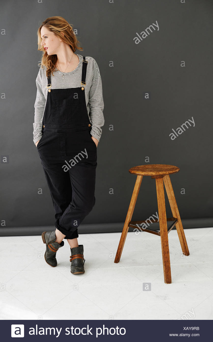 Mid adult woman standing next to stool, looking away - Stock Image