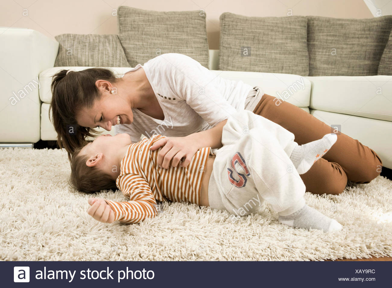 Mother and son are romping in living room, smiling - Stock Image