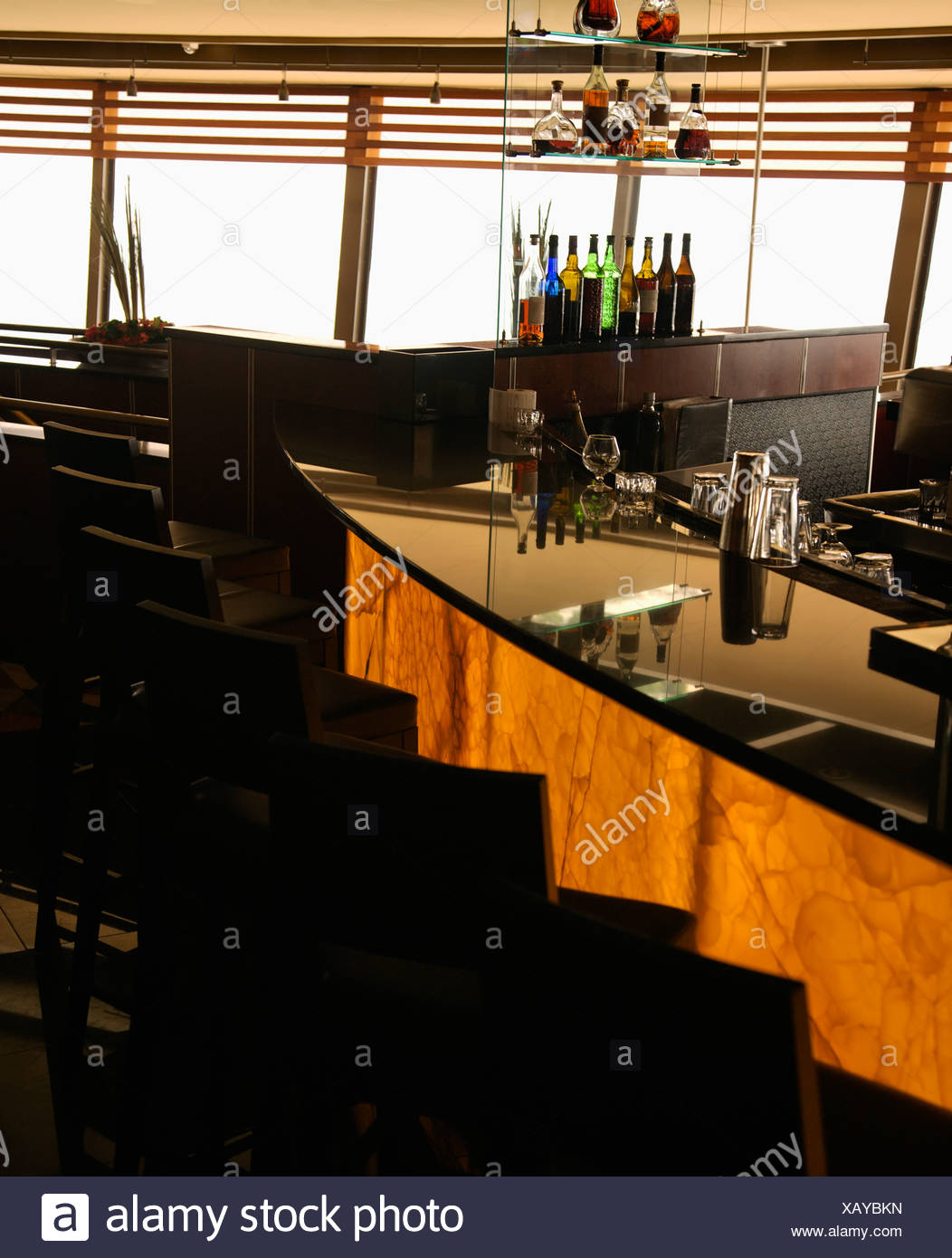 empty bar in restaurant with row of barstools and windows in