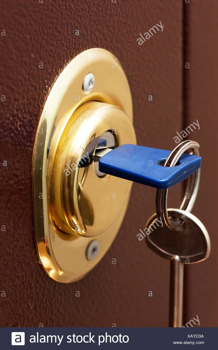 Keys and secure lock in steel door of new apartment - Stock Image