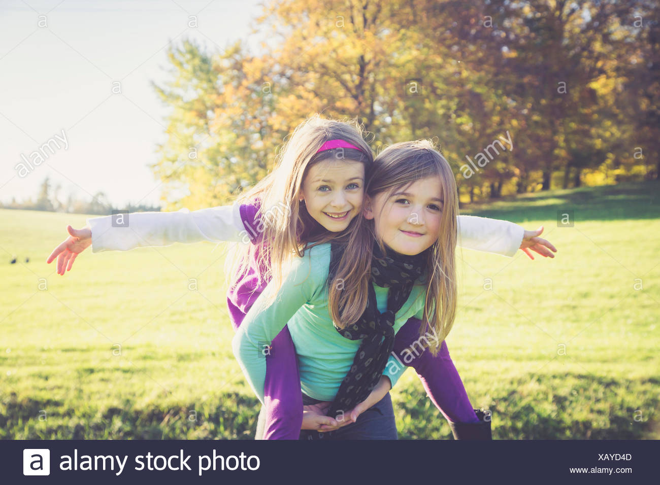 Girl giving another little girl a piggyback - Stock Image
