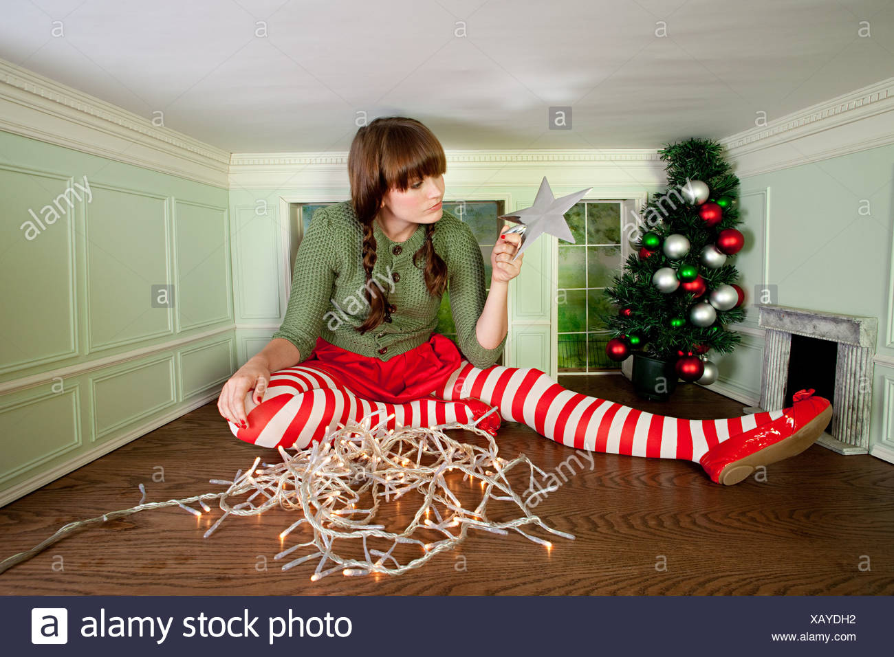 young woman in small room with christmas decorations stock image