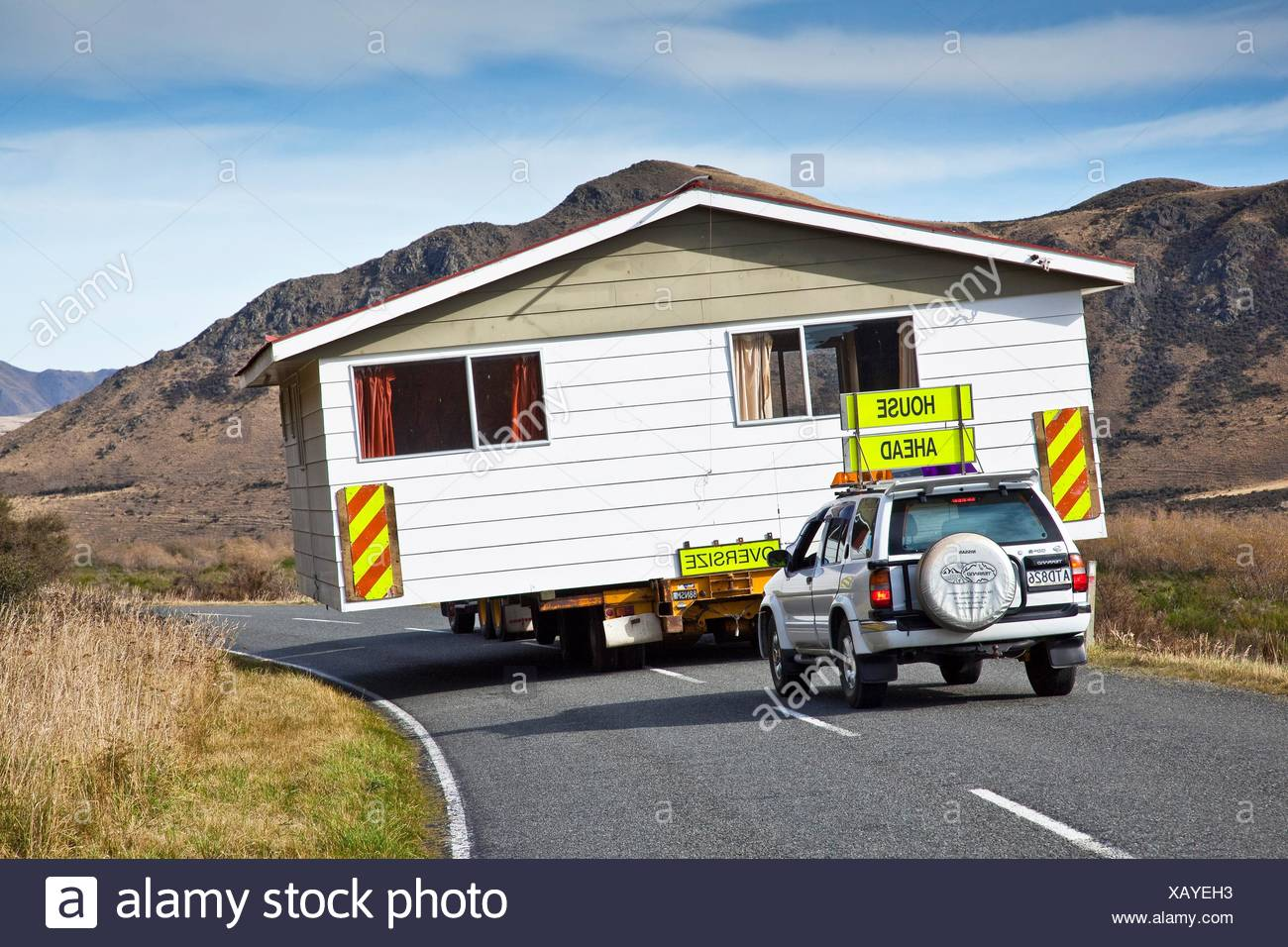 House being relocated by truck and escort vehicles, Mt. Somers, Canterbury, New Zealand Stock Photo