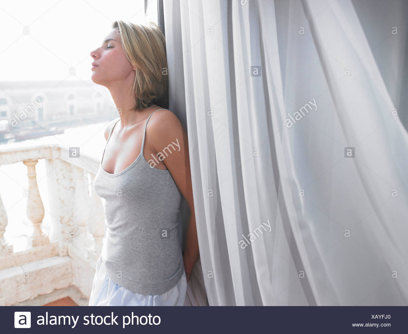 Woman in her pyjamas, on the balcony - Stock Image