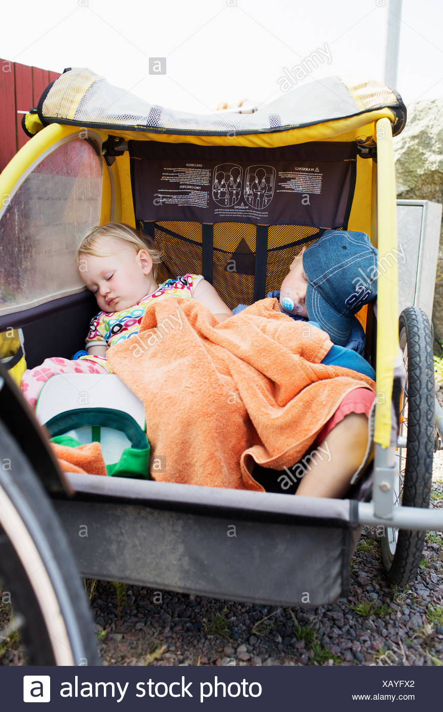 Two young children asleep in a bicycle trailer - Stock Image