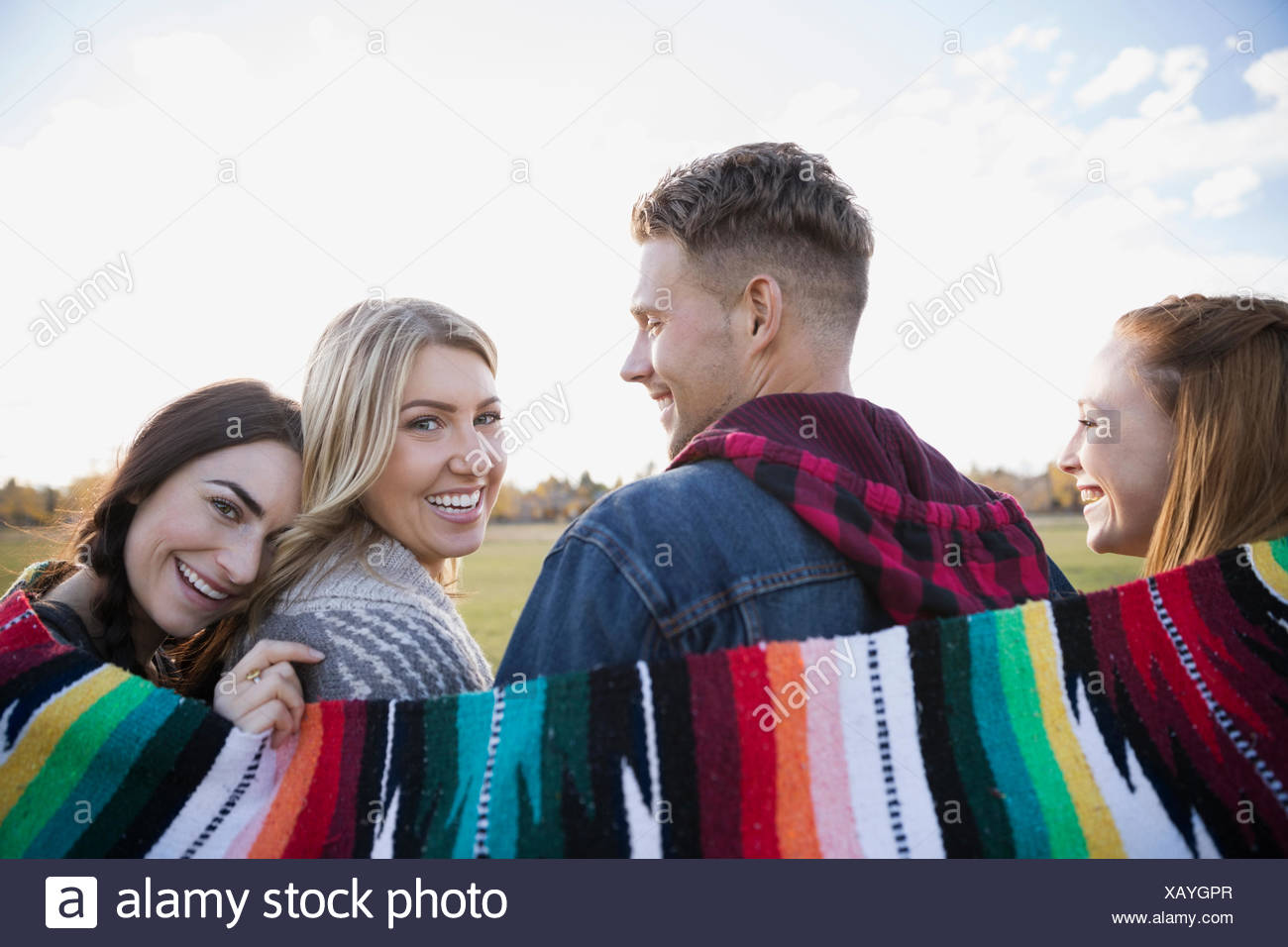 Portrait smiling friends wrapped in a blanket - Stock Image