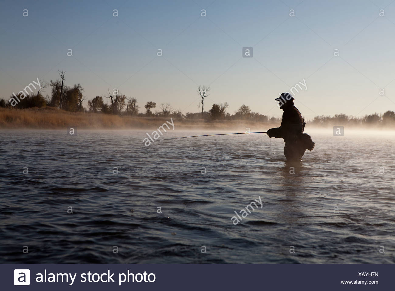 A man fishing in the early morning mist of the Green river. - Stock Image