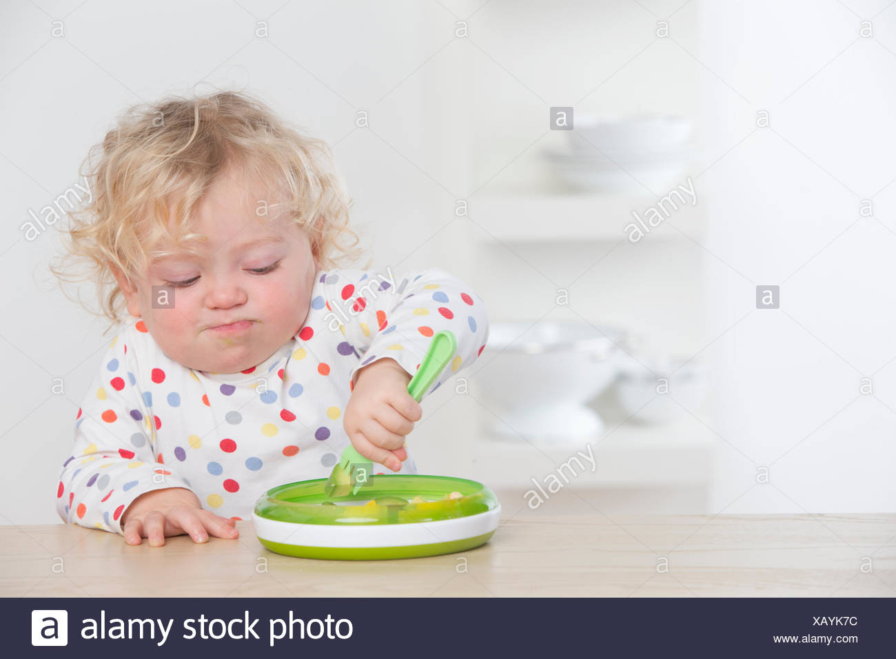 Determined baby eating avocado with fork - Stock Image