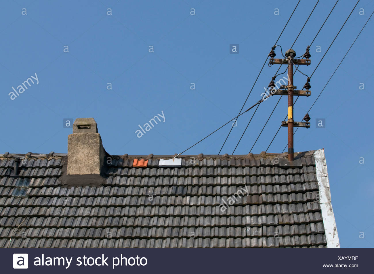 Old power lines with ceramic insulators on roof - Stock Image