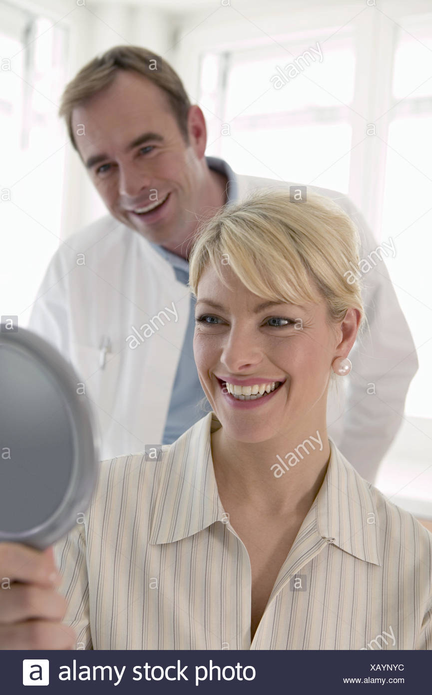 Woman smiling and looking mirror with dentist - Stock Image