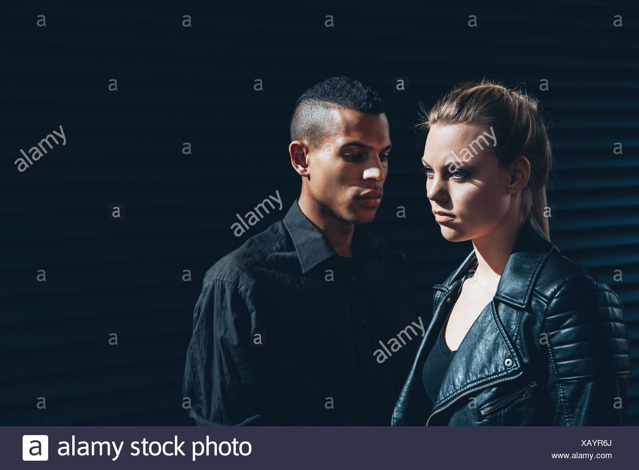 Black dressed young couple standing in front of black facade Stock Photo