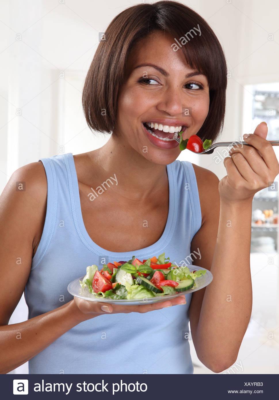 WOMAN EATING MIXED SALAD - Stock Image