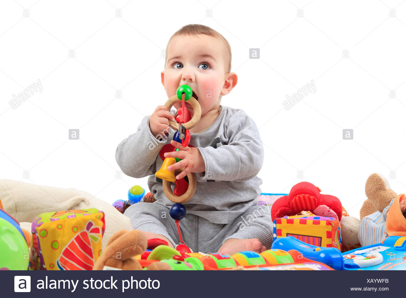 lively baby sitting in playthings and uttering something of  it - Stock Image