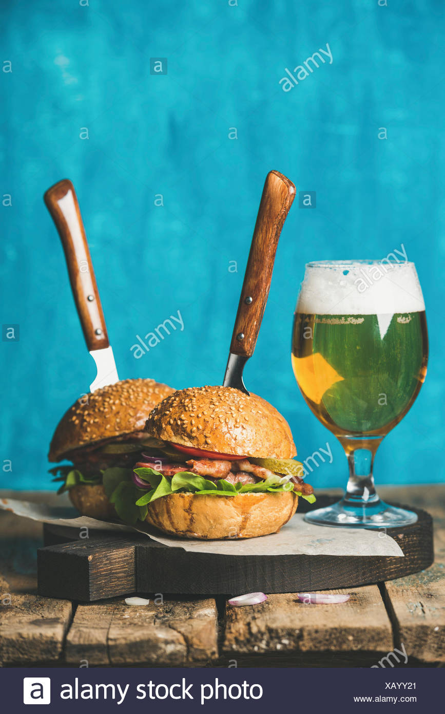 Homemade beef burgers with crispy bacon, onion, pickles, fresh vegetables, glass of wheat beer on serving wooden board over rust - Stock Image