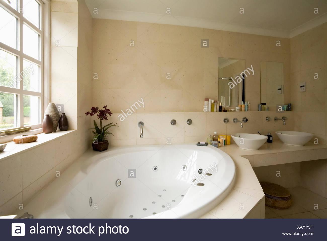 Corner Jacuzzi bath below window in modern bathroom with limestone ...