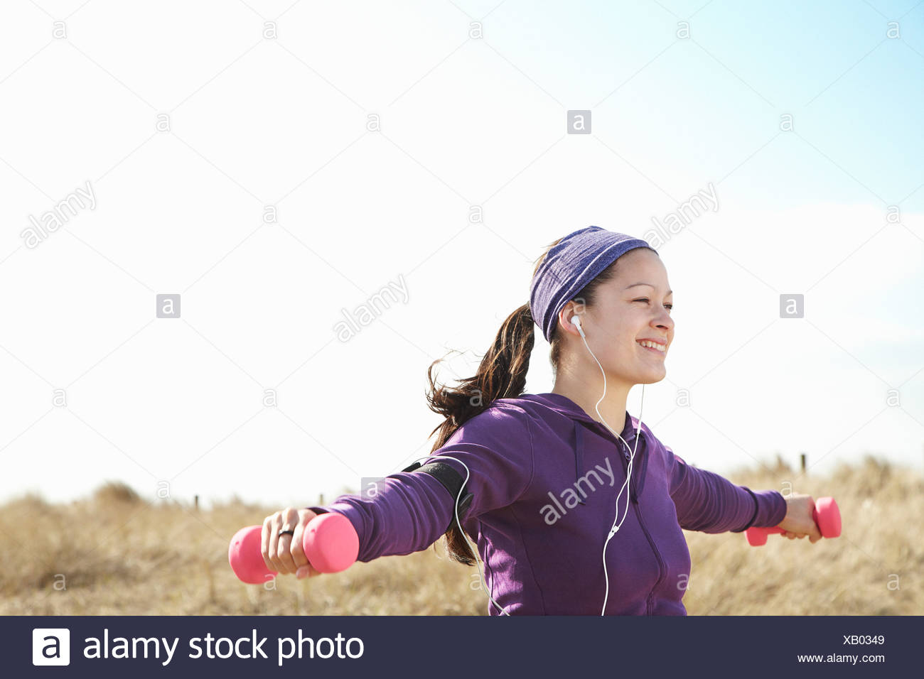 Smiling woman lifting dumbbells outside - Stock Image