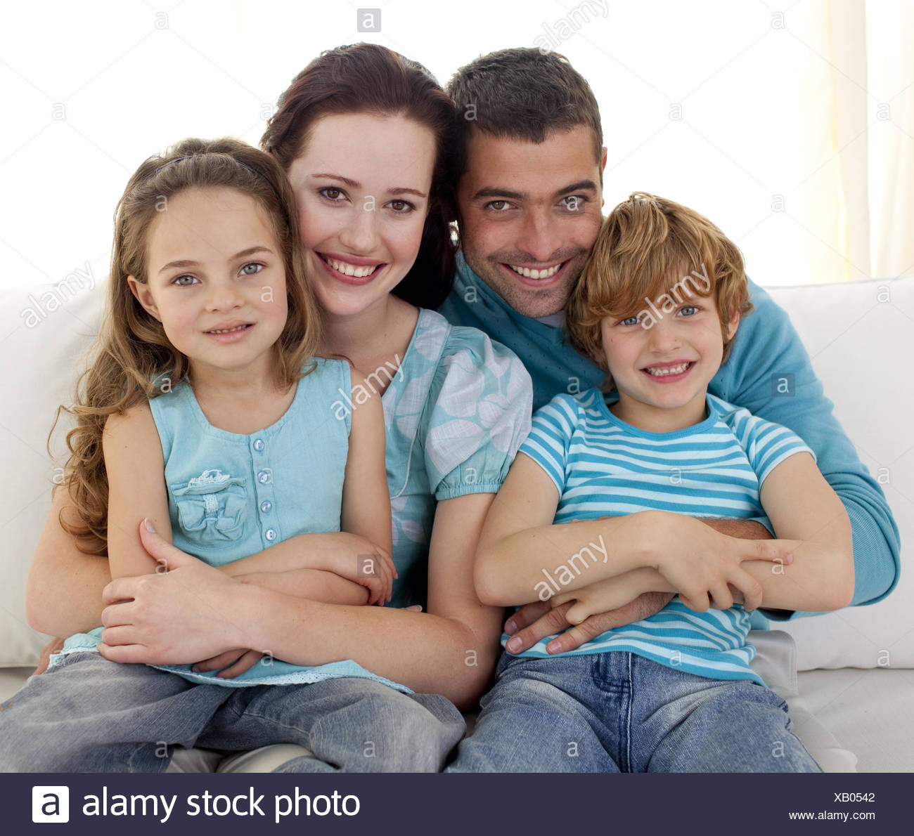 Family sitting on sofa together - Stock Image