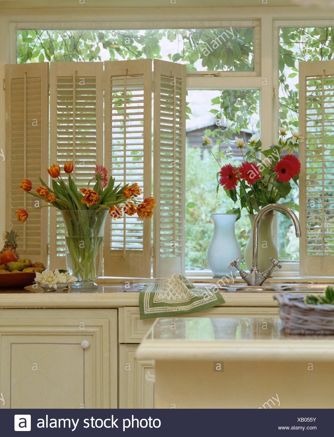 Red Gerberas And Orange Striped Tulips In Glass Vases On