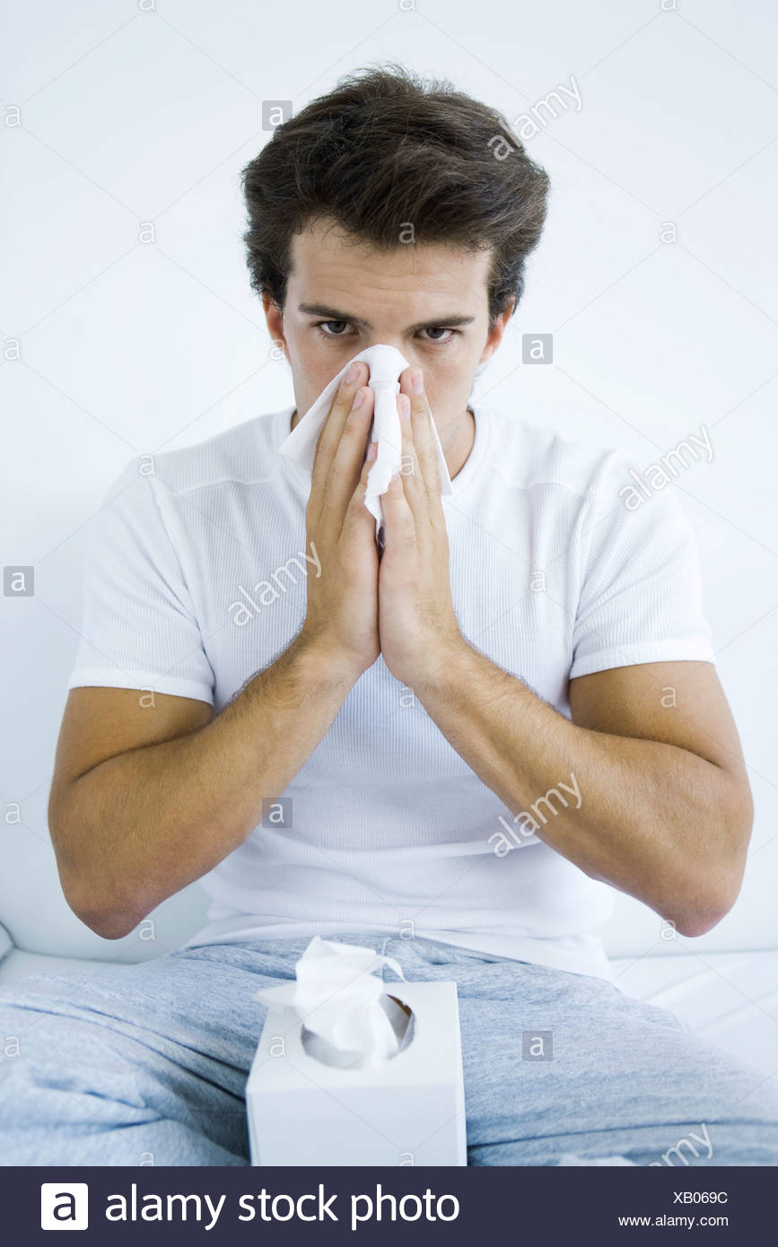 Man blowing his nose with a tissue, looking at camera - Stock Image